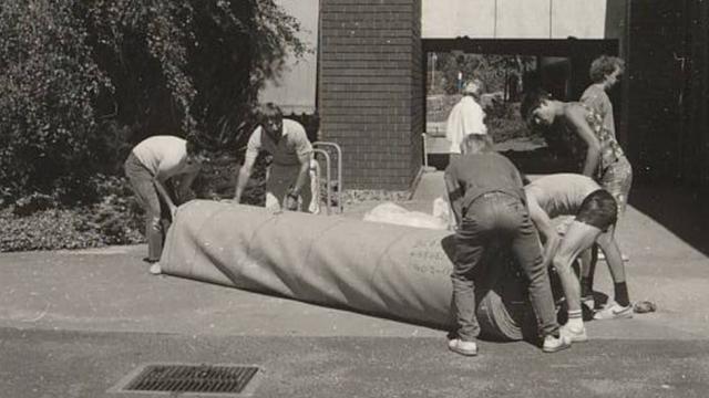 Image of Deakin staff rolling long carpet