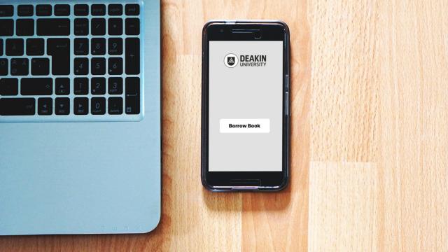 Mobile phone with Deakin Borrow app on a wood table