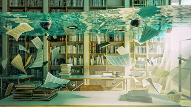 Stock image of water in a library with books and papers floating