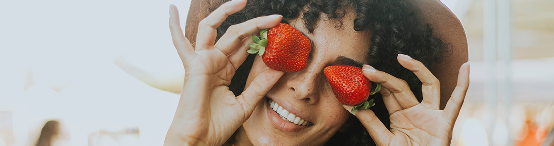 Woman holding strawberries over her eyes