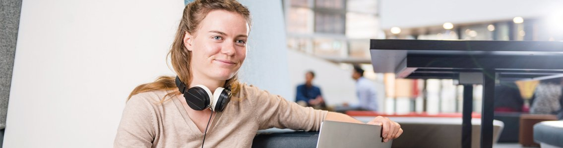 student wearing headphones smiles while working on laptop1