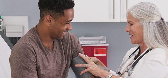 Male having blood pressure taken by nurse