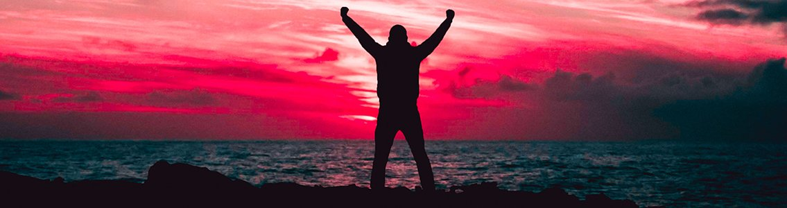 Silhouette of man raising arms against sunset