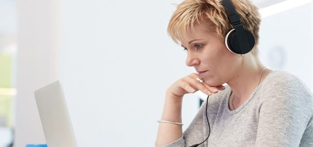 Woman wearing headphones and looking at laptop screen