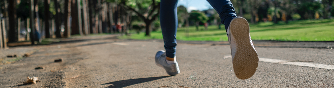 close up of person's feet while running outside in park