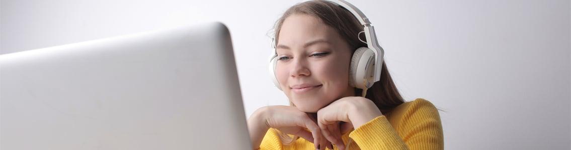 woman wearing headphones and watching laptop screen