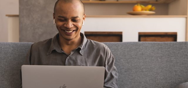 man smiling as he types on laptop at home wearing headphones