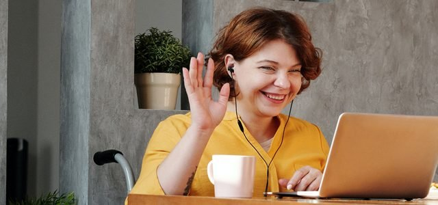 Woman smiling and waving at laptop