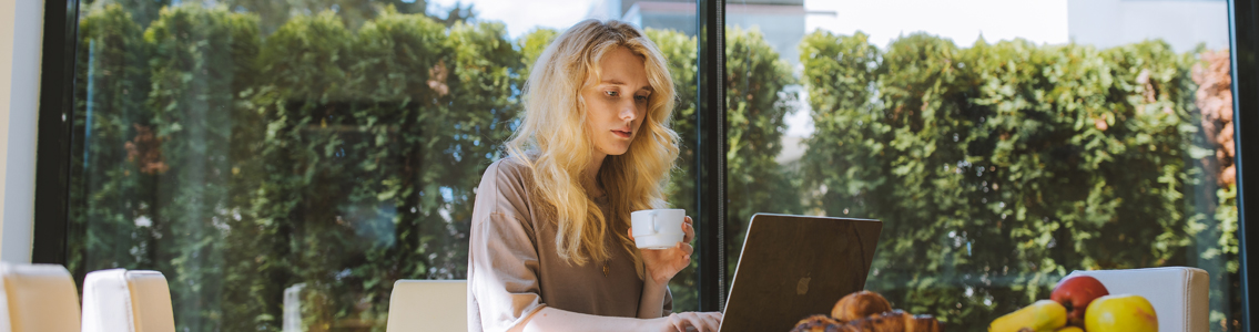Woman holding coffee cuo as she types on laptop on table at home