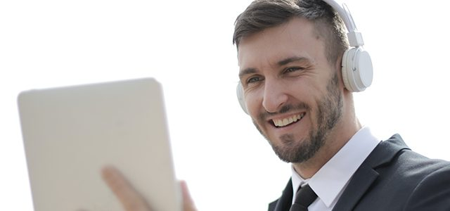 Smiling man wearing headphones and holding tablet