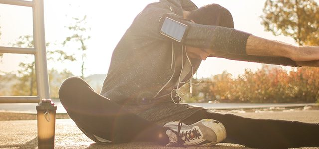 Runner stretching and wearing smartphone