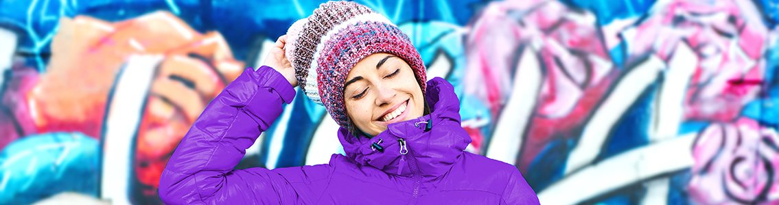 Smiling girl in beanie and purple jacket