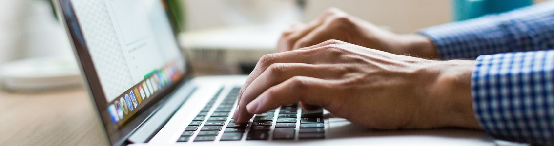 close-up of hands typing on laptop
