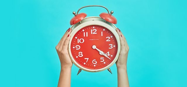 woman's hands holding up clock against cyan background