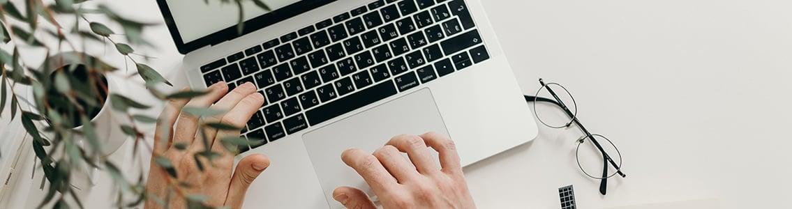 Close-up shot of hands on laptop keyboard