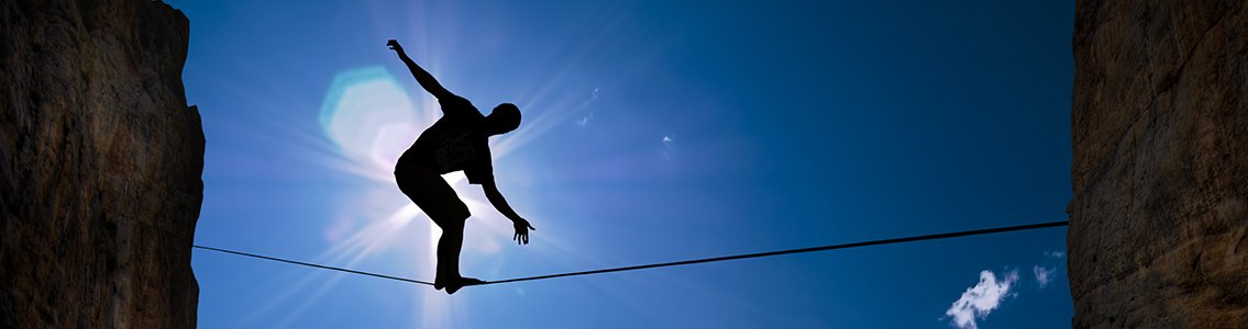 Silhouette of person balancing on tightrope