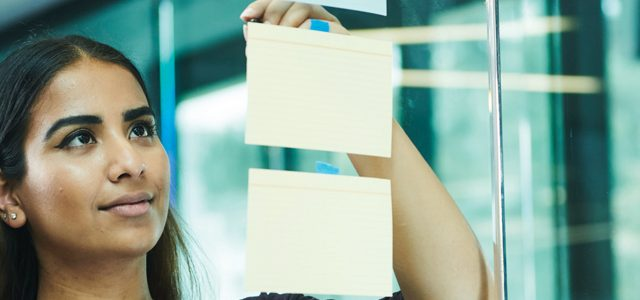 student sticking Post-its on glass office wall