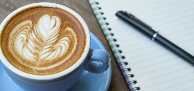 coffee next to notebook and pen