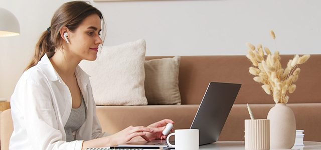 woman wearing headphones and studying on laptop in living room at home