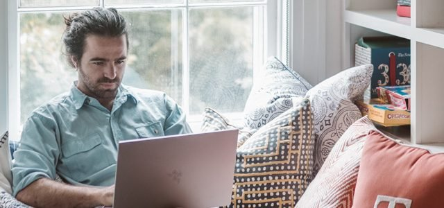 man working on laptop in living room at home