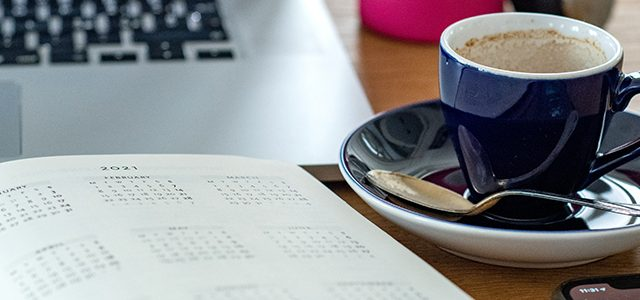 Diary, computer, phone, coffee cup