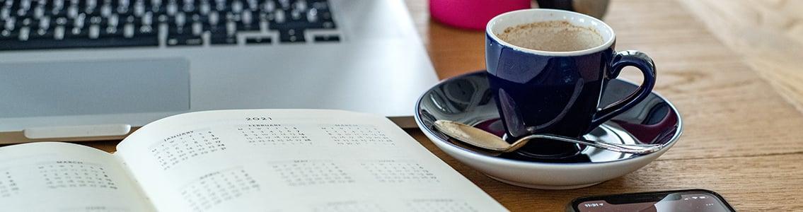 Diary, computer, phone, coffee cup