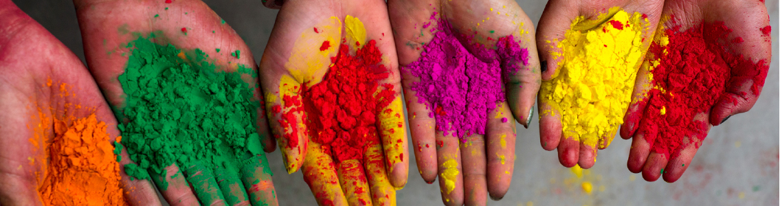 row of open-palm hands holding colourful powder