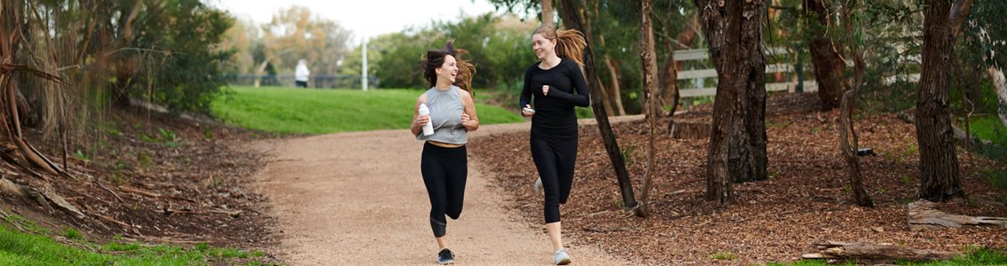 Two students smiling as they jog together outside at Burwood