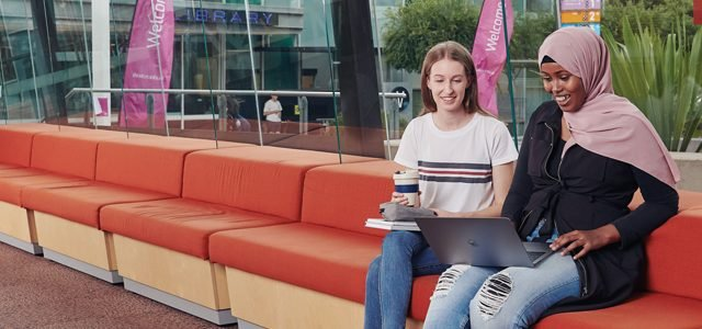 Two students smiling as they look at laptop together at Burwood Campus