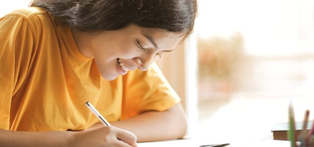 Student smiling as she writes at her desk