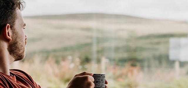 Young make looking out window holding mug