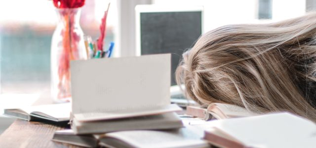 Frustrated student face-down in textbooks at desk