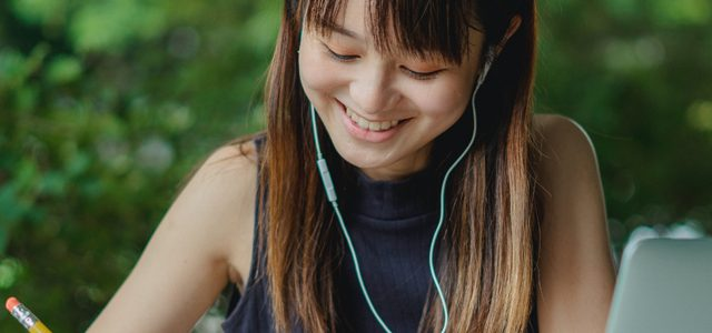 Smiling student wearing headphones while studying outside