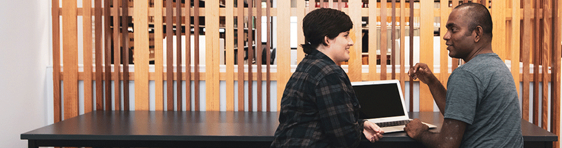 Two students chatting at desk in library