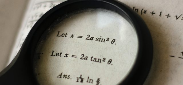 Magnifying glass resting on an open maths book