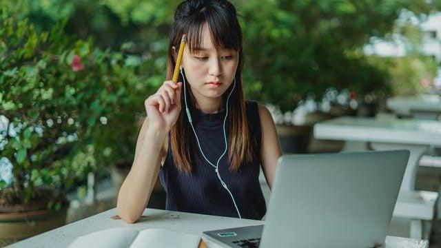 Female student with headphones on laptop