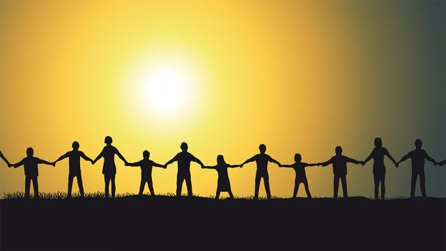 Silhouette of people holding hands in front of sun