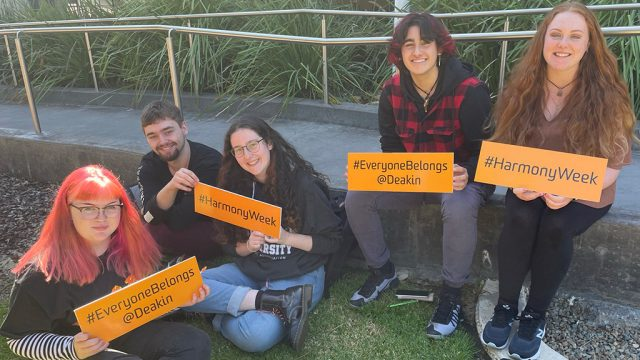 Group of Deakin students holding signs in support of Harmony Day