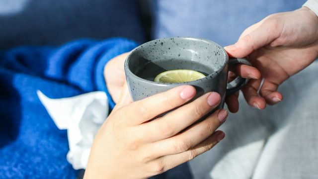 Cropped shot of person accepting cup of tea