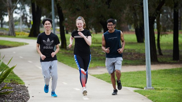 Three students jogging outside at Waurn Ponds Campus