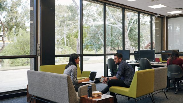 Two students chatting while seated in study area at Waurn Ponds library