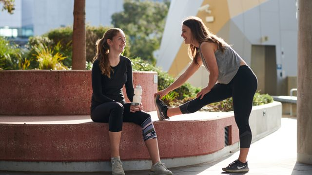 Two female students chat as they cool down after a workout at Burwood