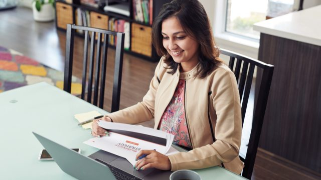 Student smiling as she works on laptop at home