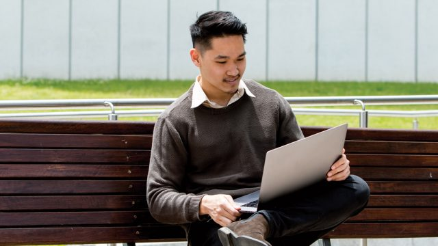 Student smiling as he works on laptop outside