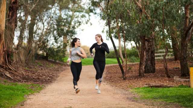 Two students running outside at Burwood Campus