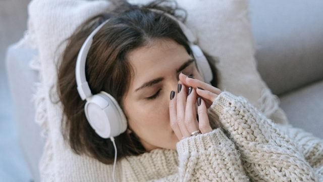 Woman wearing headphones lying down with eyes closed