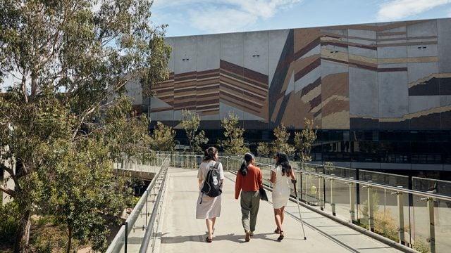 Three students walking across Burwood Campus