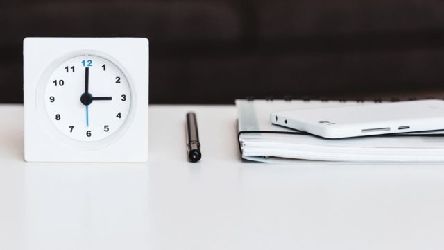 Clock, pen and notebook resting on table