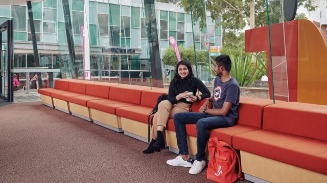 Two students smile as they chat indoors at Burwood Campus
