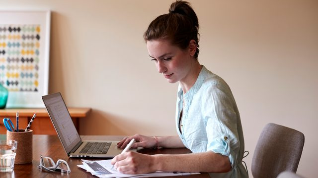Female student at desk with laptop and notes